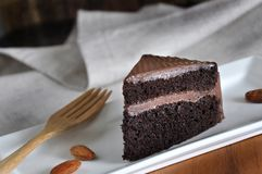 Close up Piece of Chocolate Cake with Wooden Fork. On white plate stock photo