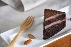 Close up Piece of Chocolate Fudge Cake. On white plate with wooden fork stock photography