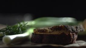 A close-up of a piece of fat lays down on a piece of brown bread. Sandwich with bacon in spices near a green onion stock video footage