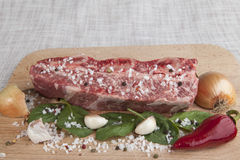 Close-up piece of fresh marbled beef, chili pepper, parsley, onion, garlic, ribs lie on a wooden tray Royalty Free Stock Images