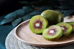 Close up Piece of Red Kiwifruit. Clsoe up piece of red kiwifruit on wooden plate royalty free stock photo