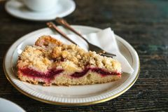 Close-up piece of sweet pie with dessert fork on a plate on a wooden surface. Close-up - piece of sweet pie with dessert fork on a plate on a wooden surface Stock Photo