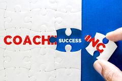 Close up piece of white jigsaw puzzle with COACHING and SUCCESS. Text , concept of business coaching bring to success completion , human resource training for royalty free stock photography
