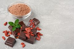 Close-up pieces of dark chocolate bar with dried Goji berries, glass bowl of cocoa powder and mint Stock Photos