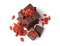 Close-up pieces of dark chocolate bar with dried Goji berries Stock Photo