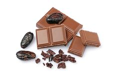 Close-up pieces of milk chocolate bar with cocoa beans Stock Photos