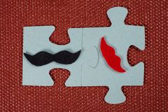 Close-up of 2 pieces of puzzle. A symbolic man with a mustache and a woman with lips. The concept of psychological compatibility Stock Photos