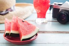 Close up pieces of watermelon with tourist items on rustic table. Summer holiday Royalty Free Stock Photos