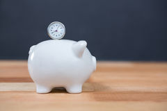 Close-up of piggy bank and clock. Close-up of pink piggy bank and clock on wooden table Royalty Free Stock Photo