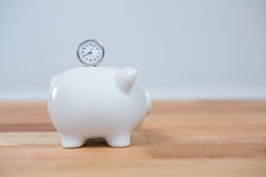 Close-up of piggy bank and clock. Close-up of pink piggy bank and clock on wooden table Stock Photo