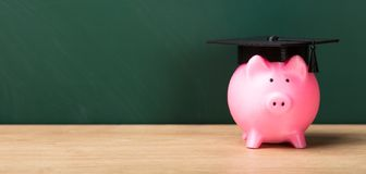 Close-up Of A Piggy Bank With Graduation Cap. In Front Of Green Chalkboard stock photo