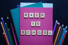 Close-up pile of books, school stationery, wooden words back to school on slate black background. Back to school concept Royalty Free Stock Images