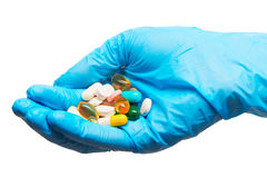 Close up of pile of different tablets and capsules on female doctor's hand in blue sterilized surgical glove. Against white background Stock Photo