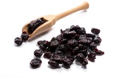 Close-up of pile dried, raw blueberries in a wooden spoon on white background royalty free stock image