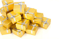 Close up of a pile of gold gifts on white Stock Photography