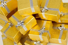 Close up of a pile of gold gifts on white Royalty Free Stock Image