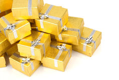 Close up of a pile of gold gifts on white Royalty Free Stock Photos