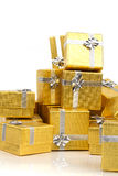 Close up of a pile of gold gifts on white Stock Image