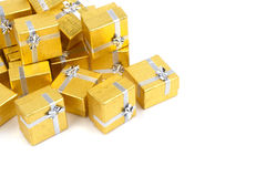Close up of a pile of gold gifts on white Stock Photos