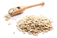 Close-up of pile of oat flakes in a wooden spoon on white backgr stock images