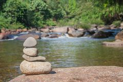 Close up pile of pebbles with beautiful landscape view of small waterfall in the river with water stream flowing through stone. Royalty Free Stock Images