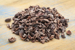 Raw cacao nibs. Close-up of a pile of raw cacao nibs on a grunge wooden background stock images