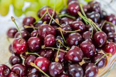 Close up of pile of ripe cherries with stalks and leaves. Large collection of fresh red cherries. Ripe cherries stock images