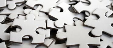 Close-up of a pile of uncompleted elements of a white puzzle. A huge number of rectangular pieces from one large white mosaic.  Stock Photography