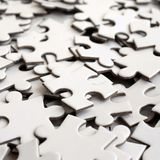 Close-up of a pile of uncompleted elements of a white puzzle. A huge number of rectangular pieces from one large white mosaic. Close-up of a pile of uncompleted royalty free stock photos