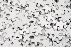 Close-up of a pile of uncompleted elements of a white puzzle. A huge number of rectangular pieces from one large white mosaic.  royalty free stock photos