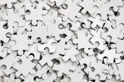 Close-up of a pile of uncompleted elements of a white puzzle. A huge number of rectangular pieces from one large white mosaic royalty free stock image