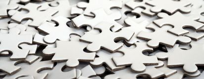 Close-up of a pile of uncompleted elements of a white puzzle. A huge number of rectangular pieces from one large white mosaic.  stock images
