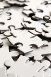 Close-up of a pile of uncompleted elements of a white puzzle. A huge number of rectangular pieces from one large white mosaic.  stock photos