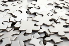 Close-up of a pile of uncompleted elements of a white puzzle. A huge number of rectangular pieces from one large white mosaic.  royalty free stock images