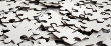 Close-up of a pile of uncompleted elements of a white puzzle. A huge number of rectangular pieces from one large white mosaic.  stock image
