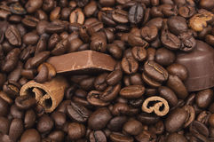 Close up of piled coffee beans, cinnamon sticks and chocolate Royalty Free Stock Photography