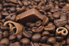 Close up of piled coffee beans, cinnamon sticks and chocolate Stock Images