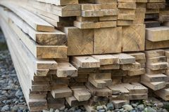 Close-up of piled stack of natural brown uneven rough wooden boa stock photos