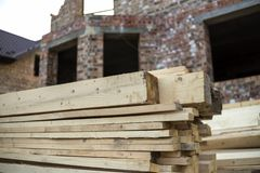 Close-up of piled stack of natural brown uneven rough wooden boards lit by bright sun. Industrial timber for carpentry, building,. Repairing and furniture stock photos