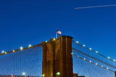 Close up of a pillar of the Brooklyn bridge with flag at night Royalty Free Stock Photography