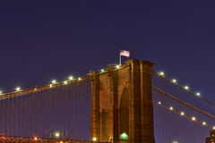 Close up of a pillar of the Brooklyn bridge with flag at night Stock Photos