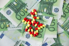 Close up of pills or drugs and euro cash money. Medicine, healthcare and drug trafficking concept - close up of medical pills or drugs and euro cash money royalty free stock images