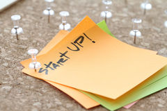 Close up on pin and start up word on sticky note Stock Image