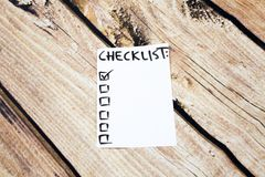 Close up of pin and to do list Checklist word on sticky note with wooden background Royalty Free Stock Images