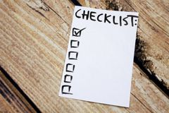 Close up of pin and to do list Checklist word on sticky note with wooden background Royalty Free Stock Photography