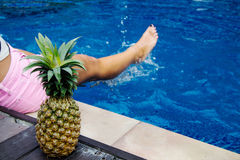 Close-up of pineapple and female leg in the swimming pool Royalty Free Stock Photos