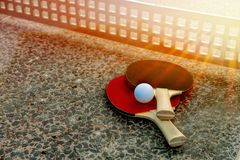 Close up of ping-pong ball with tennis rackets on stone tennis table in sunny lights, Equipment for outdoors table Stock Photography