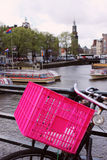 Close up of a pink bicycle basket with tour boats behind. These pink baskets are seen on many black bicycles in Amsterdam. Here tour boats can be seen in the Royalty Free Stock Images