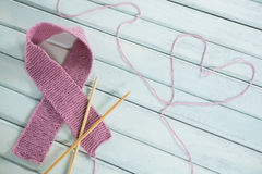 Close-up of pink Breast Cancer Awareness ribbon by crochet needles with heart shape Royalty Free Stock Photography