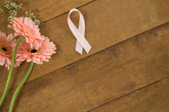 Close-up of pink Breast Cancer Awareness ribbon by gerbera flowers Royalty Free Stock Photos